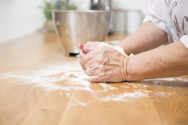 mature hands kneading dough