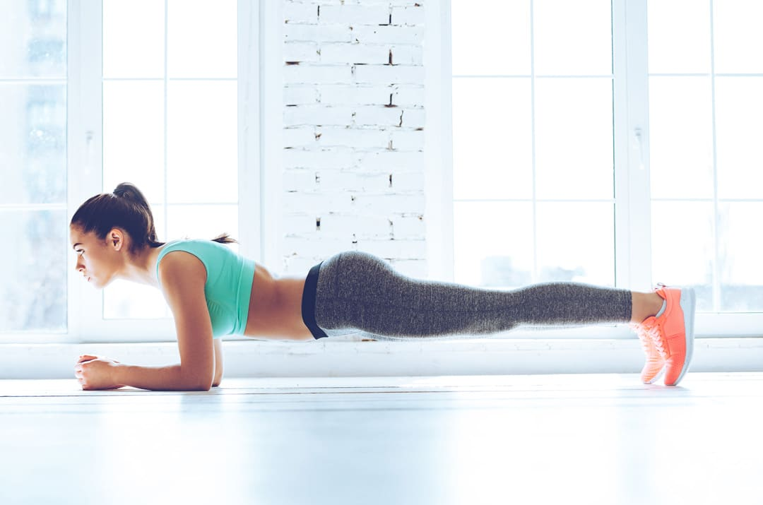 woman with a nice tan doing planks